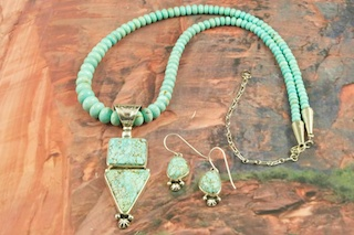 Outstanding Necklace and Earrings Set. Genuine Number 8 Mine Turquoise set in Sterling Silver Pendant. Number 8 mine Necklace featuring Sterling Silver Beads, Cones and Clasp. Plus Beautiful Number 8 Turquoise Earrings. Created by Navajo Artist Lucy Valencia. Signed L. J. by the artist. This is a one of a kind piece. The photo is of the jewelry you will be receiving. The Number 8 mine is located in Eureka County Nevada. Since 1976 there has been no Number 8 Turquoise mined. There is however, an existing stock pile that Mr. Dowell Ward, the last owner of the Number 8 mine, had stocked away for later sorting. The Turquoise is a collector's item--because once the reserve is gone there will be no more material released onto the market. The Gold Mining Company owns the claim to the Number 8 mine and it has been swallowed up by the gold mining operations. This is some of the last Number 8 Turquoise to be had and will be a great addition to your collection.